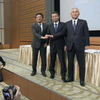 Kawasaki Kisen Kaisha Ltd. President Eizo Murakami (left), Mitsui O.S.K. Lines Ltd. President Junichiro Ikeda (center) and Nippon Yusen KK President Tadaaki Naito join hands after announcing in Tokyo on Monday that they will merge their container operations. | KYODO