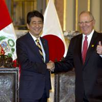 Peruvian President Pedro Pablo Kuczynski shakes hands with Japan's Prime Minister Shinzo Abe after signing bilateral agreements at the government palace in Lima on Friday. | AP