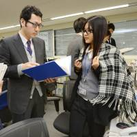 An Environment Ministry staffer wears a stole to keep warm on Tuesday as the government began a nationwide Warm Biz energy-saving campaign the same day. | KYODO