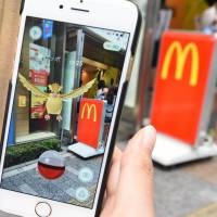 A woman plays 'Pokemon Go' game on her smartphone in front of a McDonald's restaurant in Tokyo's Akihabara shopping district.  | AFP-JIJI