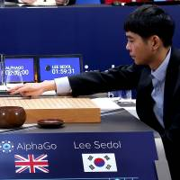 Lee Sedol makes the first move in a game against AlphaGo in April. | REUTERS