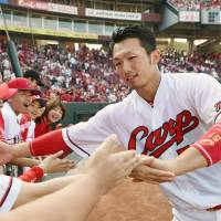 The Carp's Seiya Suzuki celebrates with fans after his walk-off home run in June. | KYODO