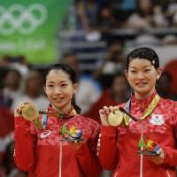 Japan's Misaki Matsutomo (left) and Ayaka Takahashi react after receiving the gold medal in women's doubles badminton at the 2016 Summer Olympics in Rio de Janeiro. | AP