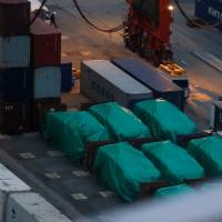 Six of the nine armored troop carriers belonging to Singapore, from a shipment detained at a container terminal, are seen in Hong Kong on Thursday. | REUTERS
