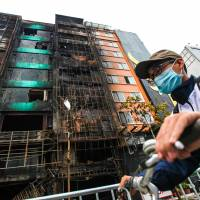 Buildings damaged by a fire that gutted a karaoke bar in Hanoi, killing 13 people, are seen on Wednesday, a day after the deadly blaze started. | AFP-JIJI