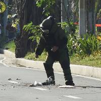 A police bomb squad member prepares to carry out a controlled detonation near a suspicious package found near the U.S. Embassy in Manila on Monday. | AFP-JIJI
