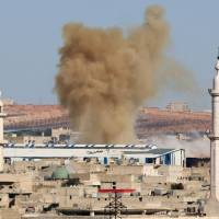 Smoke rises from a rebel held neighborhood of Aleppo, Syria, Thursday. | REUTERS