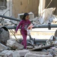 A girl makes her way through the debris of a damaged site that was hit Wednesday by airstrikes in the rebel held al-Shaar neighborhood of Aleppo, Syria, Thursday. | REUTERS