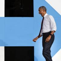 U.S. President Barack Obama reacts to seeing supporters as he walks on stage at PNC Music Pavilion in Charlotte, North Carolina, on Friday during a campaign rally for Democratic presidential candidate Hillary Clinton. | AP