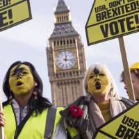 Demonstrators hold placards calling on Americans to vote and avoid getting 'Brexited' in the U.S. presidential election at a demonstration organized by global civic movement Avaaz, at Parliament Square in London on Thursday. | AP IMAGES FOR AVAAZ