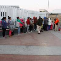 Central Americans and Mexicans line up to apply for U.S. asylum Thursday at a crossing in Tijuana, Mexico. | REUTERS
