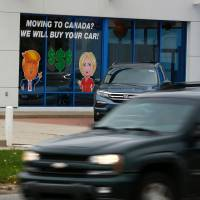 A painted sign in the window of a Honda dealership in Detroit shows the frustration of voters who did not support Donald Trump. | AFP-JIJI