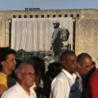 A large portrait of Cuba's late President Fidel Castro hangs from a building while people wait in line to pay tribute to Castro in Havana Monday. | REUTERS