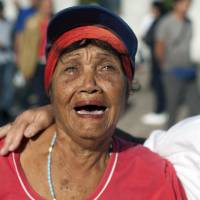 A woman weeps as she walks past the monument in honor of independence hero Jose Marti while paying her respects to Fidel Castro in Revolution Plaza in Havana Monday. Havana's Revolution Plaza is the site of a two-day tribute to Castro, who died late Friday. | AP