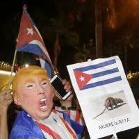 A person in a Donald Trump mask holds a sign reading, 'The rat dies' in Spanish on Saturday during a celebration in Miami of the death of longtime Cuban leader Fidel Castro. | AP