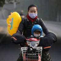 A woman and her son wearing masks ride an electric bicycle on a hazy day in Beijing on Nov. 4. The election of climate change skeptic Donald Trump as U.S. president may force China to take the lead in fight against global warming. | REUTERS