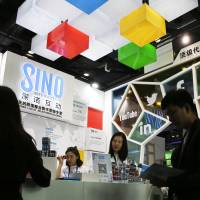 A visitor browses a booklet at a social network company booth during the 2016 Global Mobile Internet Conference in Beijing in April. China's legislature on Monday approved a cybersecurity law that human rights activists warn will tighten political controls and foreign companies say might isolate Chinese industries. | AP