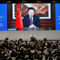 Attendees listen to a speech by Chinese President Xi Jinping shown on a screen during the opening ceremony of the third annual World Internet Conference in Wuzhen, China, on Wednesday. | REUTERS