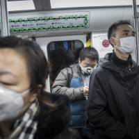 Commuters wear face masks while riding in the subway in Beijing last December. | BLOOMBERG