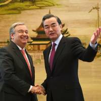 U.N. Secretary-General-designate Antonio Guterres (left) talks with China's Foreign Minister Wang Yi after a joint news briefing in Beijing on Monday. | AFP-JIJI