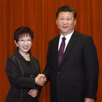 Chinese President Xi Jinping and Kuomintang Chairwoman Hung Hsiu-chu shake hands as they pose for photographers during a meeting at the Great Hall of the People in Beijing on Tuesday. | AP