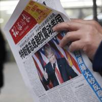A man reads a newspaper with the headline 'U.S. President-elect Donald Trump delivers a mighty shock to America' at a newsstand in Beijing on Thursday.   AP