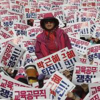 South Koreans hold up cards reading, 'Park Geun-hye should step down' during a rally against the president in Seoul on Saturday. | AP