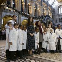 Britain's Catherine, Duchess of Cambridge, poseswith pupils from Oakington Manor Primary School, in front of Dippy the Diplodocus, as she attends a children's tea party to celebrate Dippy's time in Hintze Hall at the Natural History Museum in London Tuesday. | REUTERS