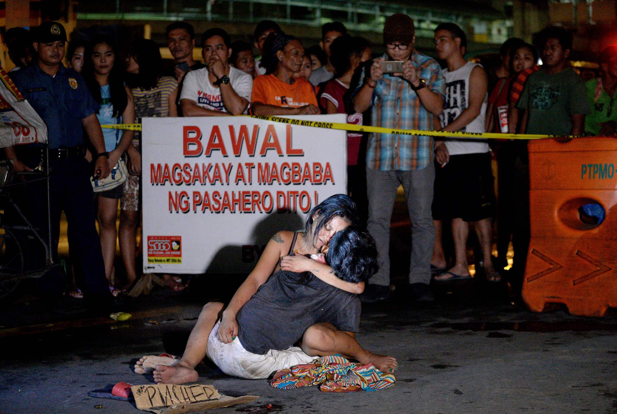 A placard reading 'I'm a pusher' sits next to a woman as she hugs her husband, who was shot dead by an unidentified gunman in Manila in July.   AFP-JIJI