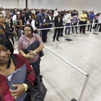 Kanockwa Horton (left), from Stone Mountain, and Jacqueline Merritt, from Atlanta, stand first in line at the Airport Community Job Fair in Atlanta on Oct. 19. | AP