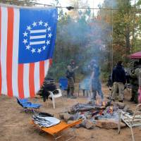 As the camp fire burns, members of the Three Percent Security Force militia gather for a field training exercise in Jackson, Georgia, on Oct. 29.   REUTERS