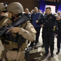 A man is escorted away by law enforcement officers moments after Republican U.S. presidential candidate Donald Trump was rushed offstage by Secret Service agents during a campaign rally in Reno, Nevada, on Saturday. | AP