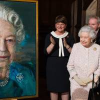Britain's Queen Elizabeth II acknowledges applause as (from left) Arlene Foster, first minister of Northern Ireland; Martin McGuinness, deputy first minister of Northern Ireland; and Frances Fitzgerald, minister of justice and equality governor of Ireland, clap as the Queen unveils a portrait of herself by artist Colin Davidson during a Co-operation Ireland reception at Crosby Hall in London Tuesday. | JEFF SPICER / POOL PHOTO VIA AP