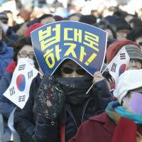 A supporter of South Korean President Park Geun-hye holds national flags during a rally opposing her resignation in Seoul on Thursday.   AP