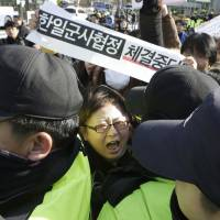 A South Korean protester scuffles with police during a rally to oppose an intelligence-sharing pact between South Korea and Japan, in front of the Defense Ministry in Seoul on Wednesday. The signs read, 'Stop the military agreement between South Korea and Japan.' | AP