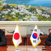 South Korean Defense Minister Han Min-koo and Japanese Ambassador to South Korea Yasumasa Nagamine sign documents related to the general security of military information agreement (GSOMIA) at the Defense Ministry in Seoul on Wednesday. | REUTERS