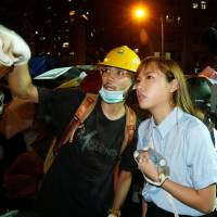 Pro-independence legislator-elect Yau Wai-ching (right) talks with a protester during a confrontation with the police outside the China Liaison Office in Hong Kong on Sunday.   REUTERS
