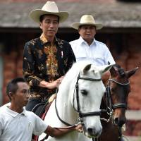 Indonesia President Joko 'Jokowi' Widodo (left) rides a horse on the outskirts of Bogor, Indonesia, on Oct. 31.   REUTERS
