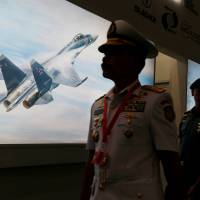 A member of Indonesia's military walks past a picture of a Sukhoi fighter jet during Indo Defence Expo in Jakarta on Wednesday.   REUTERS