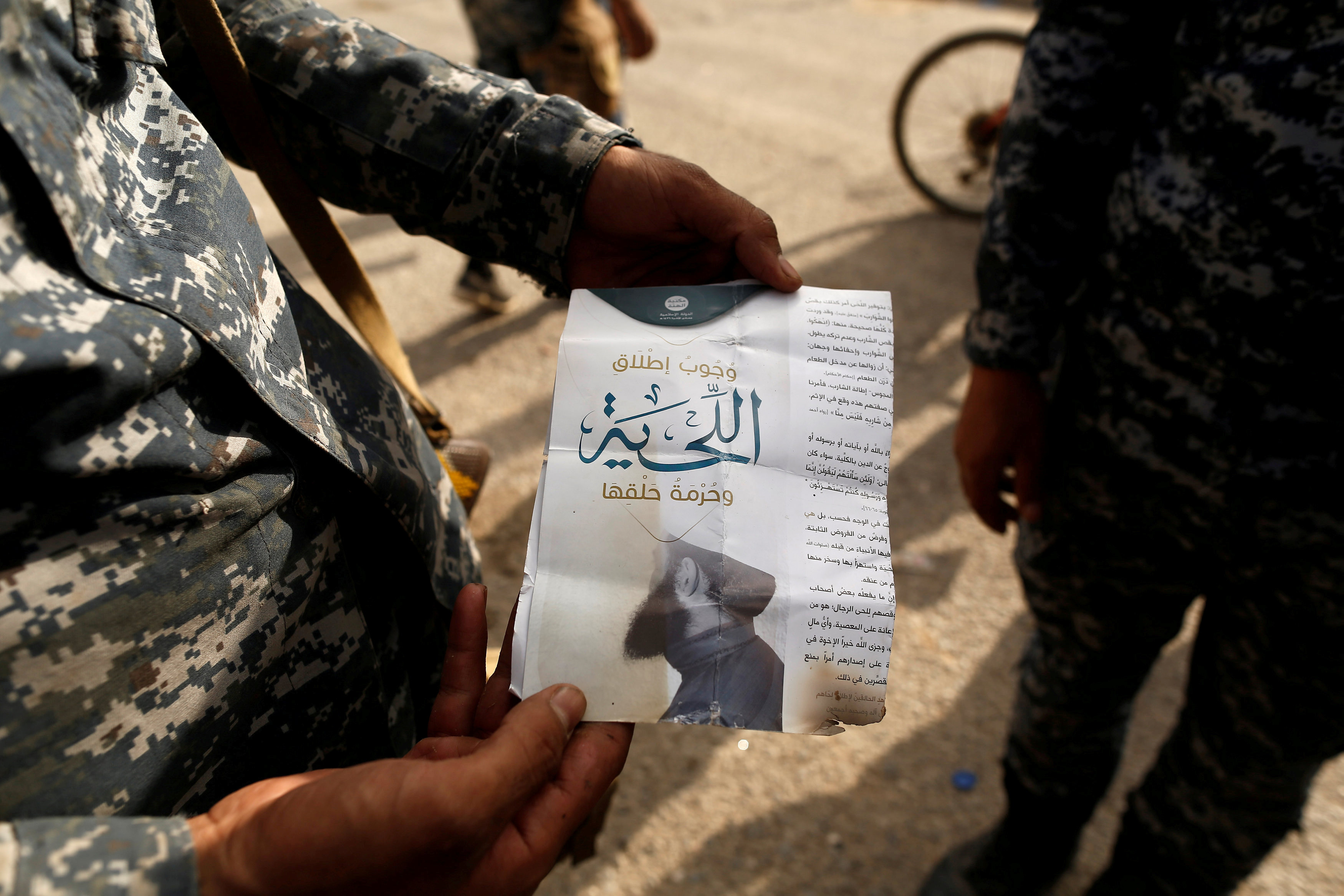 An Iraqi soldier shows a pamphlet that reads 'Wearing beards is compulsory, shaving is prohibited' along a street in the town of Shura, which was recaptured from the Islamic State group, on Saturday.   REUTERS