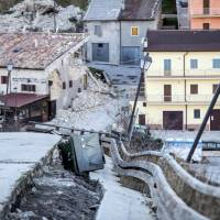 A badly damaged road is seen in Castelluccio di Norcia, central Italy, Wednesday. Authorities say more than 100,000 people were affected by the 6.6-magnitude quake on Sunday, either sustaining property damage or being frightened from their homes. | MASSIMO PERCOSSI / ANSA VIA AP