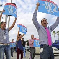 Supporters of Amendment 2 wave signs on a street corner in Fort Lauderdale, Florida, on Tuesday. | AP