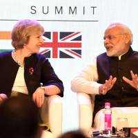 British Prime Minister Theresa May speaks with Indian Prime Minister Narendra Modi as they attend The India-U.K. Tech Summit in New Delhi on Monday. | AFP-JIJI