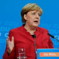 German Chancellor Angela Merkel addresses a news conference at the Christian Democratic Union party headquarters in Berlin on Sunday after earlier telling her party she will seek re-election next year. | AFP-JIJI
