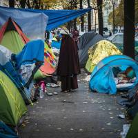 A woman looks on Thursday in Paris near to the Stalingrad metro station, one of several camps sprouting up around the French capital. Less than 300 km from the recently demolished 'Jungle' migrant camp in Calais, around 2,000 migrants are living in similar conditions on the streets of Paris. | AFP-JIJI