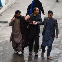 Afghan men assist a woman, who collapsed after a massive suicide blast at a Shiite mosque, to the Estiqlal Hospital in Kabul on Monday. | AFP-JIJI