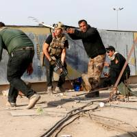 Iraqi troops offer rations to civilians after clearing third of east Mosul; smokes in high demand