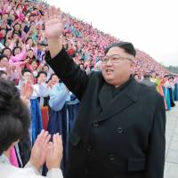 North Korean leader Kim Jong Un takes part in a photo session with participants in the Sixth Congress of the Democratic Women's Union of Korea in this undated photo released Tuesday. | REUTERS