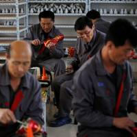 North Korean workers make soccer shoes inside a temporary factory at a rural village on the edge of Dandong, China, in October 2012. | REUTERS