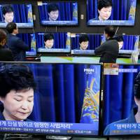 South Korean employees watch TV sets broadcasting a news report on South Korean President Park Geun-hye releasing a statement to the public in Seoul on Nov. 4. | REUTERS